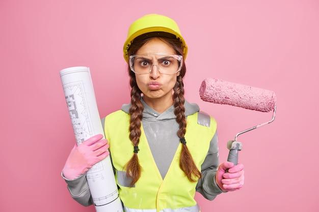 Une jeune femme grincheuse sérieuse avec deux nattes tient un rouleau de peinture et un plan