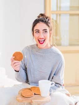 Jeune femme en gris manger