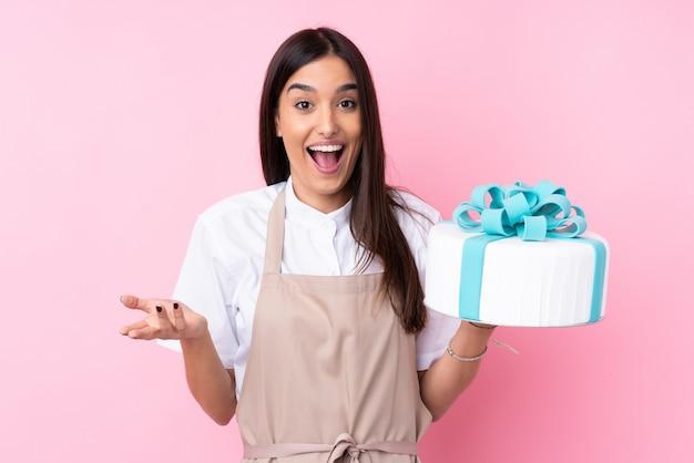 Jeune femme avec un gros gâteau avec une expression faciale choquée