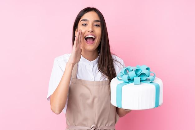 Jeune femme avec un gros gâteau sur un mur isolé criant avec la bouche grande ouverte