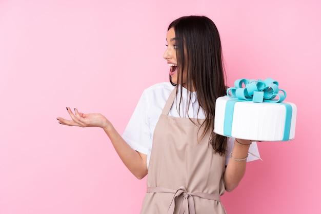 Jeune femme avec un gros gâteau sur un mur isolé avec une expression faciale surprise