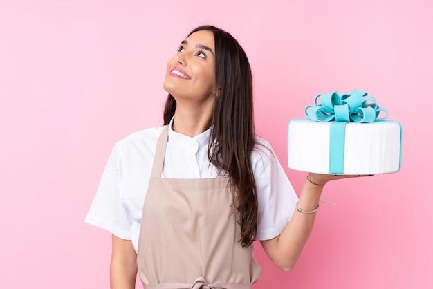 Jeune femme avec un gros gâteau sur un mur isolé en levant tout en souriant