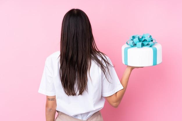 Jeune femme avec un gros gâteau sur un mur isolé en position arrière