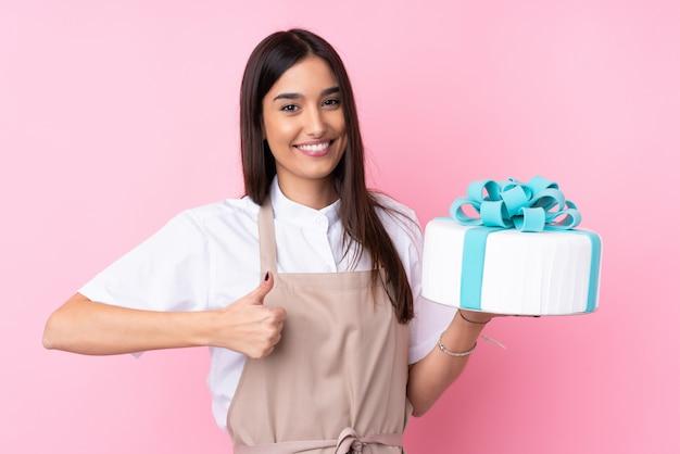 Jeune femme avec un gros gâteau sur un mur isolé avec les pouces vers le haut parce que quelque chose de bien s'est produit
