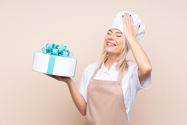 Jeune femme avec un gros gâteau sur un mur isolé a réalisé quelque chose et a l'intention de la solution