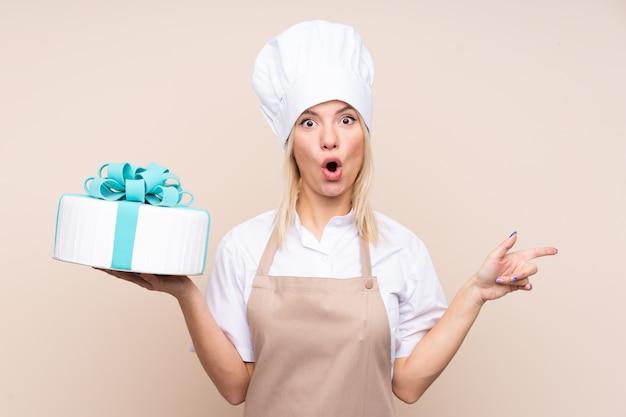 Jeune femme avec un gros gâteau sur un mur isolé surpris et pointant le côté