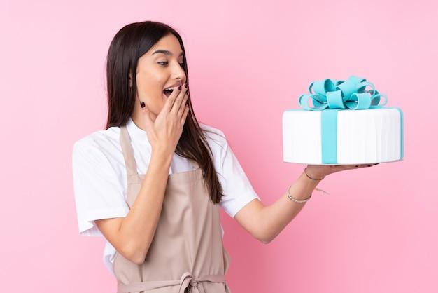 Jeune femme avec un gros gâteau sur un mur isolé avec surprise et expression faciale choquée