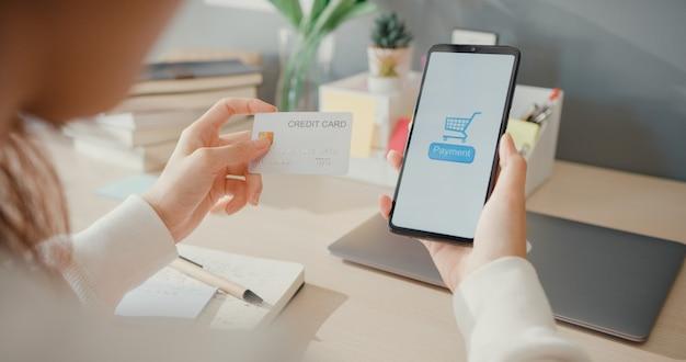 Une jeune femme en gros plan utilise un produit d'achat en ligne pour commander un téléphone portable et paie des factures avec une carte de crédit à l'intérieur du salon de la maison,