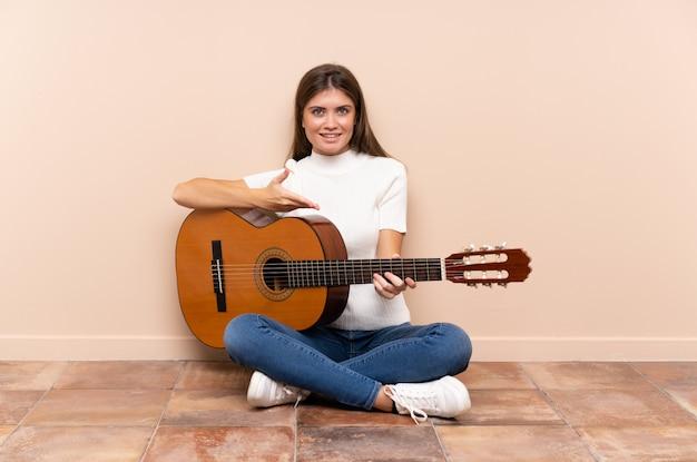 Jeune femme avec guitare assis sur le sol, étendant les mains sur le côté pour inviter à venir