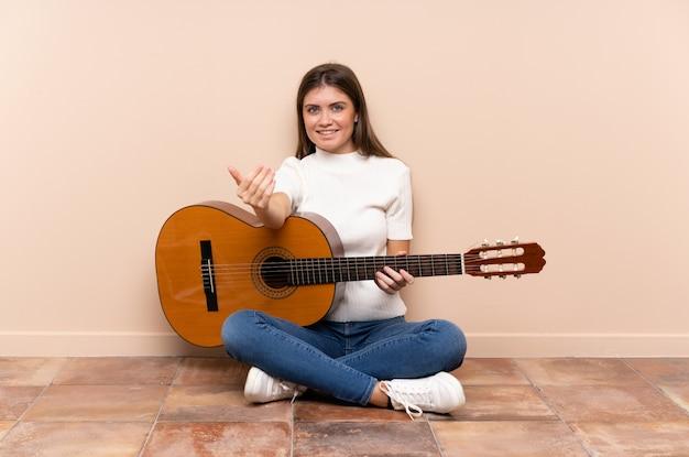 Jeune femme avec une guitare, assise sur le sol, invitant à venir