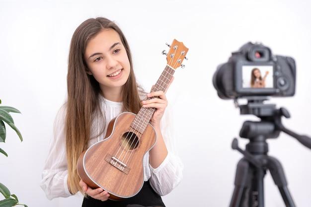 Jeune femme à la guitare créant du contenu en ligne sur fond blanc avec espace de copie