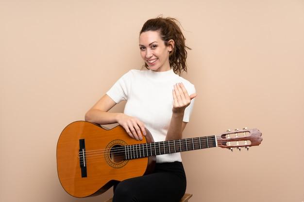 Jeune femme avec guitare invitant à venir avec la main. heureux que tu sois venu