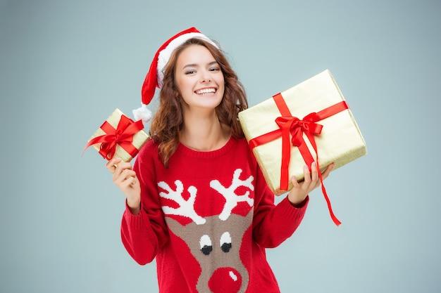 Jeune femme habillée en bonnet de noel avec des cadeaux de noël