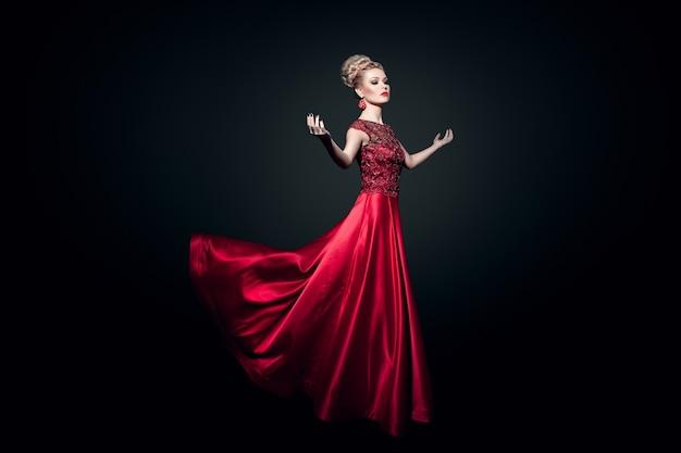 Jeune femme habillée dans une longue robe rouge fluing avec les mains levées, sur fond noir.