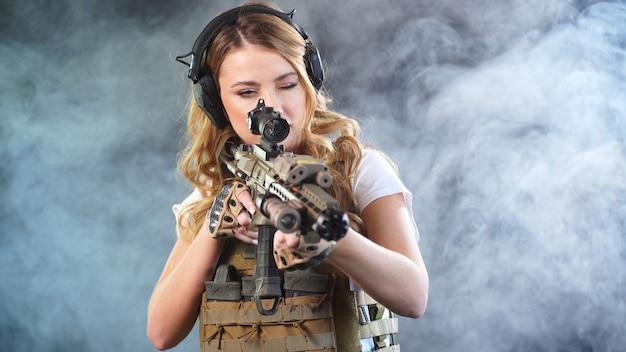 Jeune femme habillée pour l'airsoft pointe un fusil de sniper sur la cible, un fond sombre isolé en fumée.