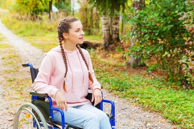 Jeune femme handicap heureuse en fauteuil roulant sur la route dans le parc de l'hôpital en attente de services aux patients. fille paralysée dans une chaise invalide pour les personnes handicapées en plein air dans la nature. concept de réadaptation.