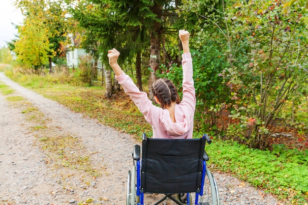 Jeune femme handicapée heureuse en fauteuil roulant sur la route dans le parc de l'hôpital jouissant de la liberté. fille paralysée dans une chaise invalide pour les personnes handicapées en plein air dans la nature. concept de réadaptation.