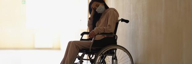Jeune femme handicapée portant un masque médical de protection assise en fauteuil roulant dans le couloir de l'hôpital