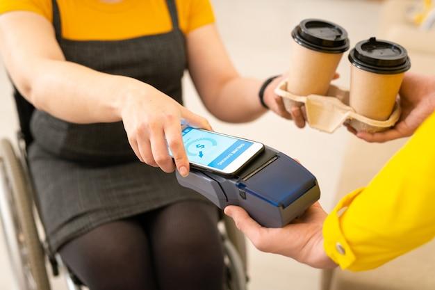 Jeune femme handicapée en tenue décontractée assis en fauteuil roulant et tenant le smartphone sur la machine de paiement tout en payant pour le café commandé