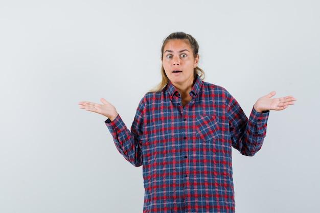 Jeune femme en haussant les épaules en chemise à carreaux et à la perplexité