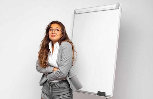 Jeune femme en haussant les épaules, se sentant confuse et incertaine, doutant des bras croisés et regard perplexe