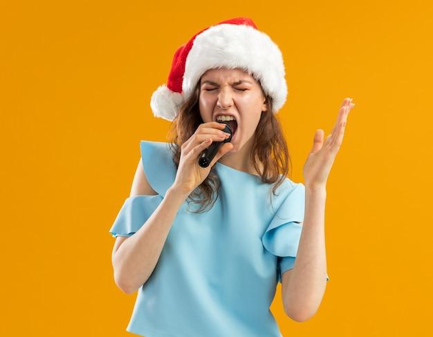 Jeune femme en haut bleu et bonnet de noel criant au microphone excité fou émotionnel avec bras levé