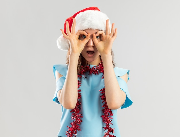Jeune femme en haut bleu et bonnet de noel avec guirlandes autour du cou à la recherche à travers les doigts faisant le geste binoculaire d'être surpris