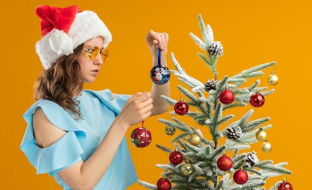 Jeune femme en haut bleu et bonnet de noel portant des lunettes jaunes tenant des boules de noël à la confusion ayant des doutes debout à côté d'un arbre de noël sur fond orange