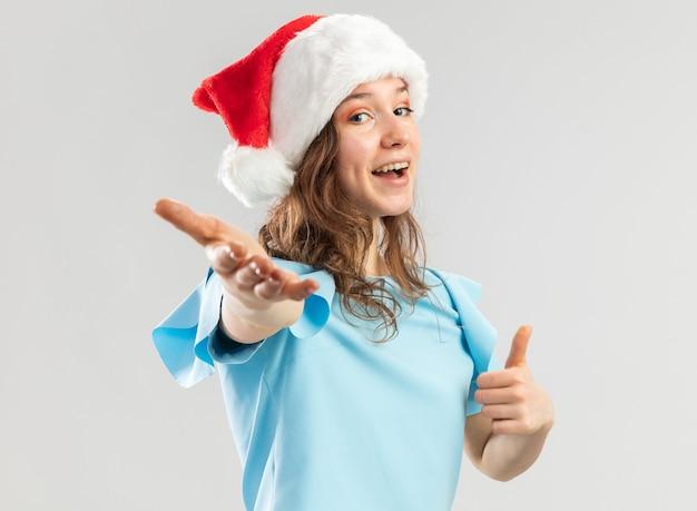 Jeune femme en haut bleu et bonnet de noel à la recherche heureuse et positive de venir ici geste avec la main