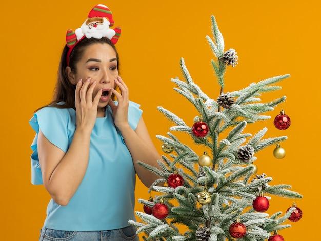 Jeune femme en haut bleu portant une jante de noël drôle sur la tête debout à côté d'un arbre de noël en le regardant être choqué avec les mains sur son visage sur fond orange