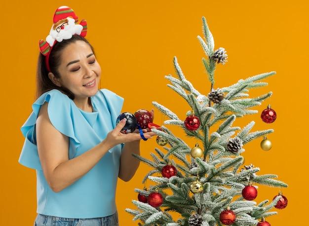Jeune femme en haut bleu portant une jante de noël drôle sur la tête debout à côté d'un arbre de noël tenant des boules de noël heureux et joyeux sur fond orange