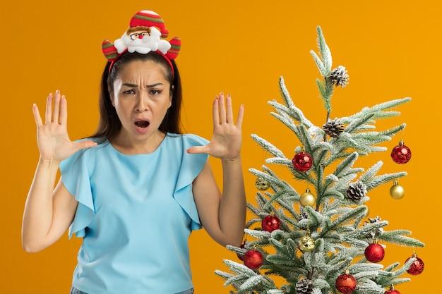 Jeune femme en haut bleu portant une jante de noël drôle sur la tête regardant la caméra avec un visage en colère criant avec les bras levés debout à côté d'un arbre de noël sur fond orange