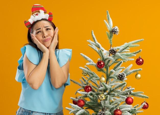 Jeune femme en haut bleu portant une jante de noël drôle sur la tête en regardant confus avec les mains sur son visage debout à côté d'un arbre de noël sur fond orange