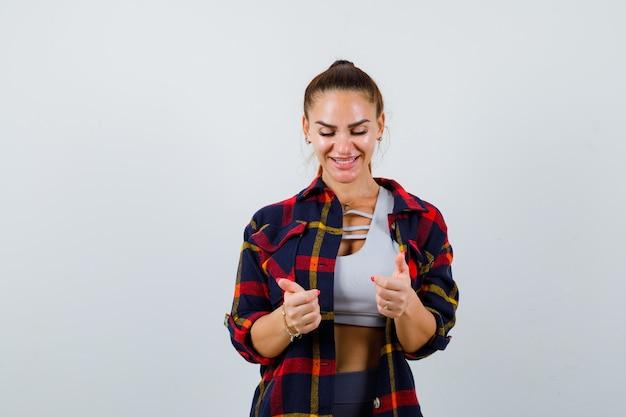 Jeune femme en haut, chemise à carreaux faisant semblant de tenir quelque chose et ayant l'air joyeux, vue de face.