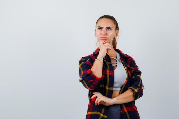 Jeune femme en haut, chemise à carreaux avec la main sous le menton et l'air pensif, vue de face.