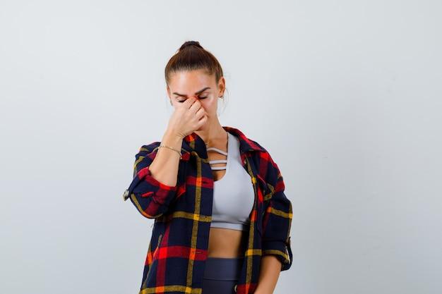 Jeune femme en haut, chemise à carreaux se frottant le nez et les yeux et ayant l'air fatiguée, vue de face.