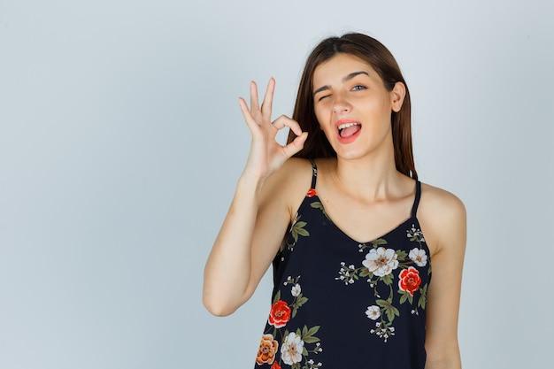 Jeune femme en haut floral montrant le geste ok, un clin de œil et à la drôle