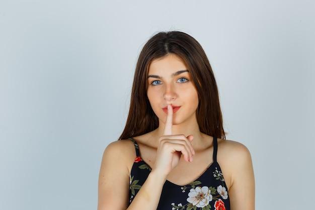 Jeune femme en haut floral montrant le geste de silence et à la sérieuse