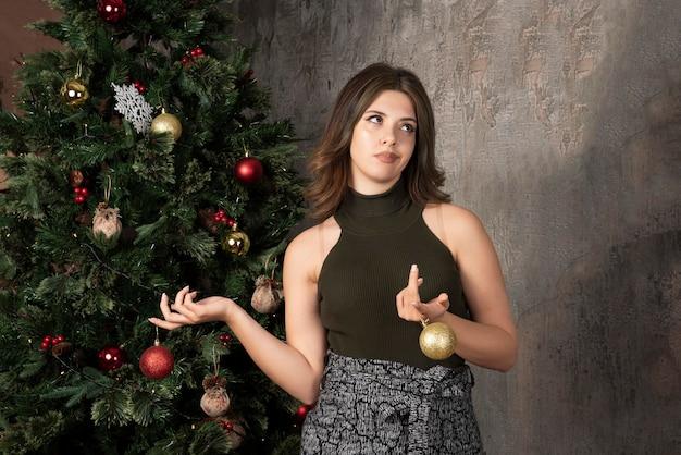 Jeune femme en haut noir tenant des boules brillantes dans une chambre décorée de noël