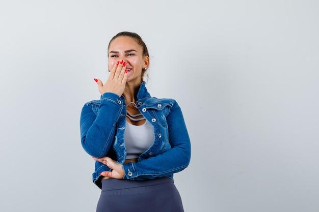 Jeune femme en haut, veste en jean avec la main sur la bouche et l'air heureux, vue de face.