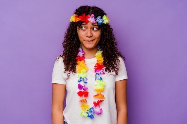 Jeune femme hawaïenne isolée sur fond violet confuse, se sent douteuse et incertaine.