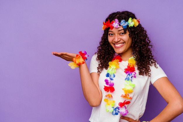 Jeune femme hawaïenne isolée sur fond violet montrant un espace de copie sur une paume et tenant une autre main sur la taille.