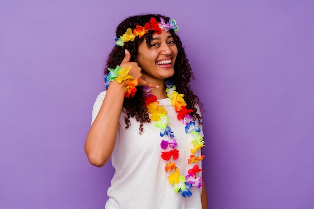 Jeune femme hawaïenne isolée sur fond violet montrant un geste d'appel de téléphone portable avec les doigts.