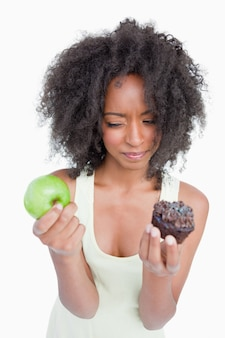 Jeune femme hésitant entre un muffin au chocolat et une pomme verte