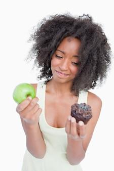 Jeune femme hésitant à peine entre un muffin et une pomme