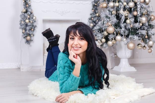 Jeune femme heureuse allongé sur un sol dans un salon avec décoration de noël