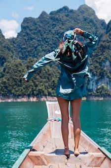 Jeune femme heureuse asiatique blogueuse touriste en costume de soie et écharpe et lunettes de soleil en vacances voyage autour de la thaïlande sur un bateau asiatique, parc national de khao sok.