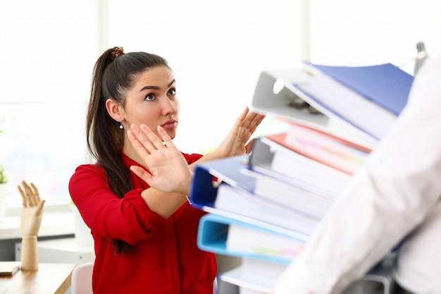 Jeune femme heureuse, assis dans le bureau et refusant de travailler avec des tas de documents