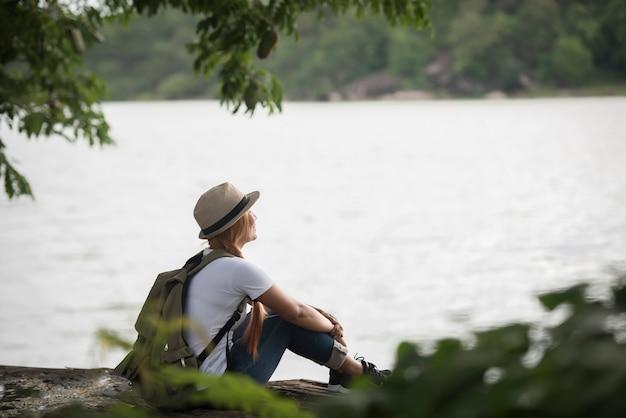 Jeune femme heureuse assise avec sac à dos profiter de la nature après la randonnée.