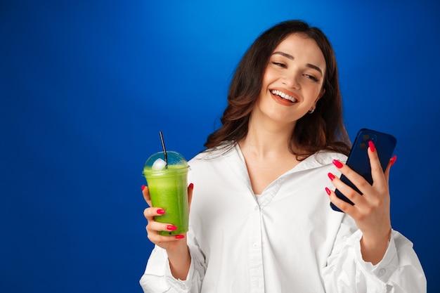 Jeune femme heureuse attirante tenant une tasse de smoothie vert et utilisant son smartphone contre b bleu...